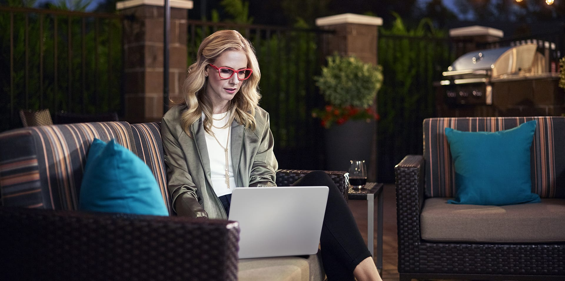 Woman sitting on patio with laptop